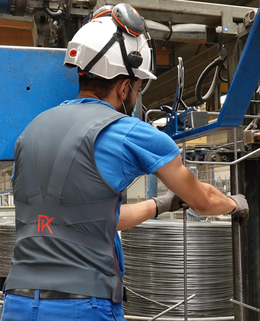 Employé BEMACO avec le gilet de protection dans l'usine d'armatures